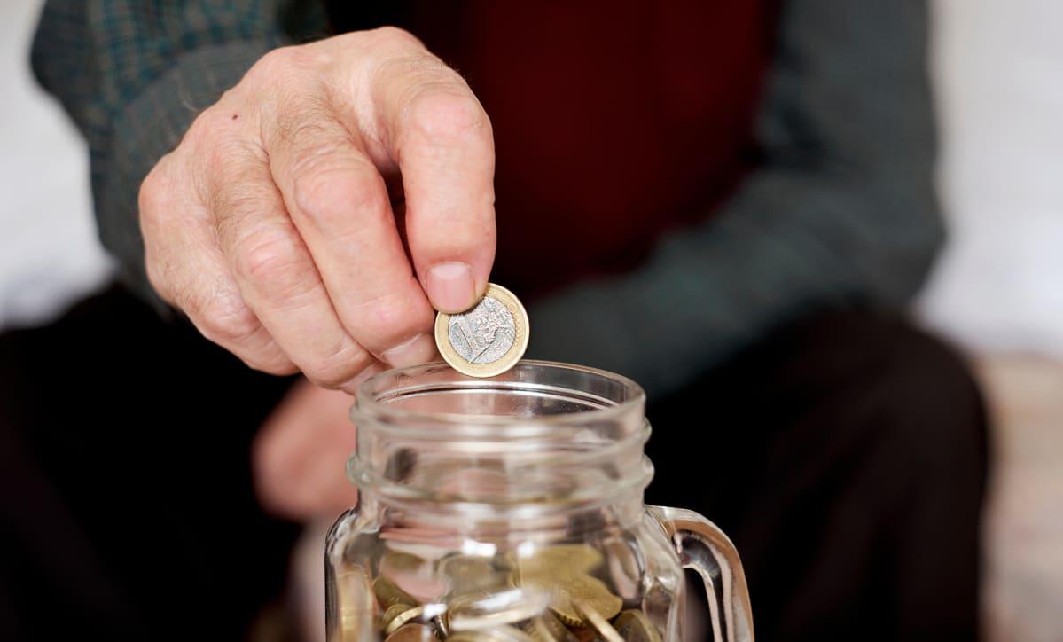 mies pudottaa euroa lasipurkkiin