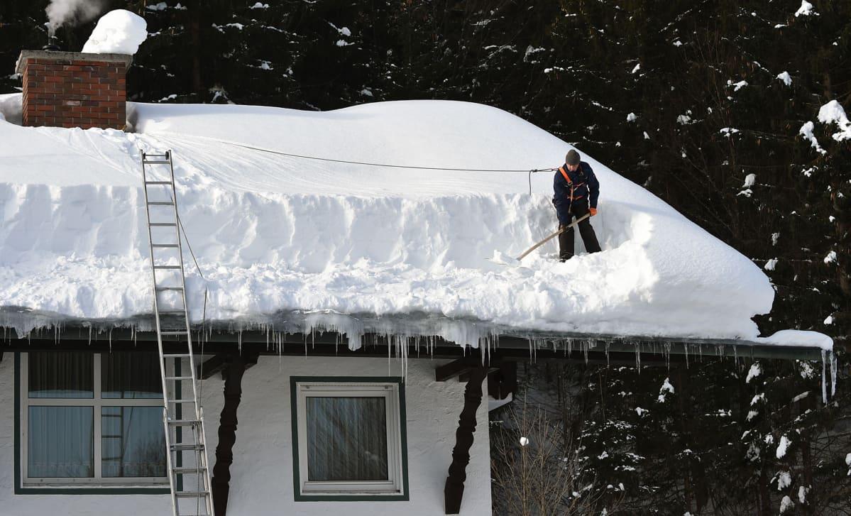 Mies pudottaa lunta katolta.