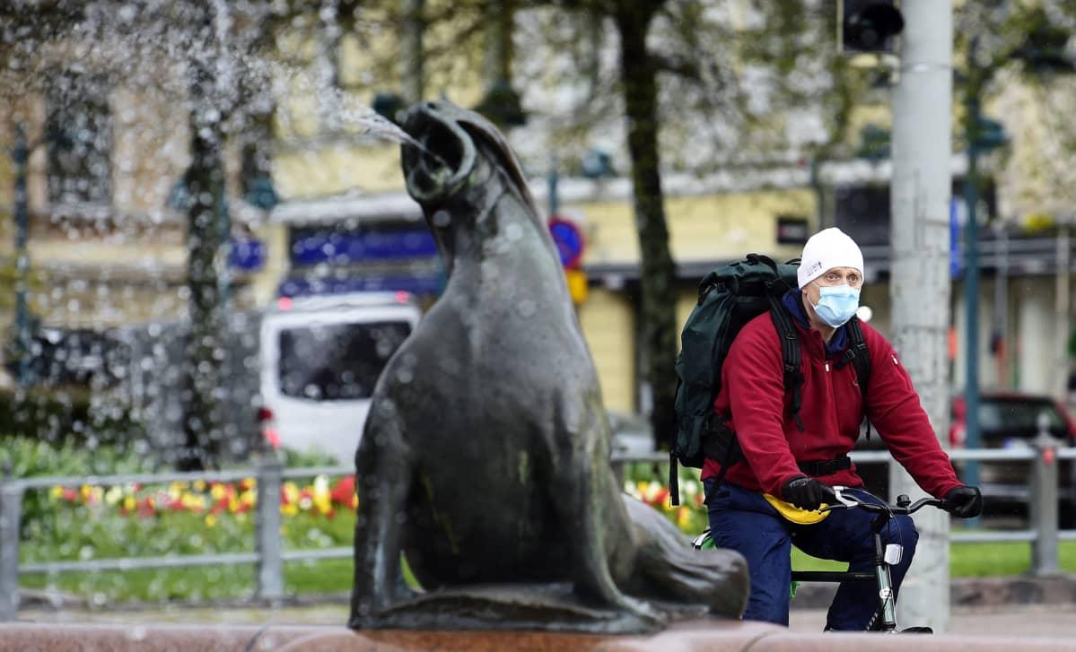 Hengityssuojainta käyttävä pyöräilijä ohittaa Havis Amandan suihkulähteen Helsingissä.