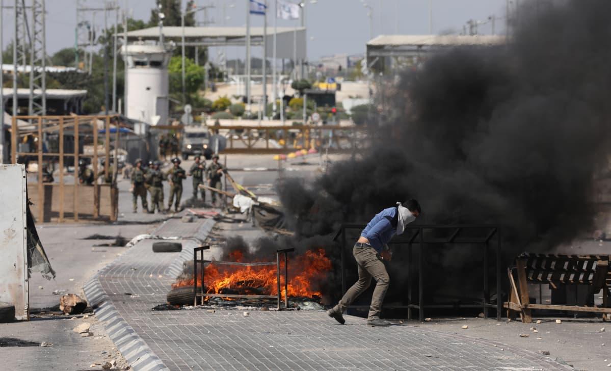 Mies kivittää israelilaissotilaita liekehtivän katusulun takaa.