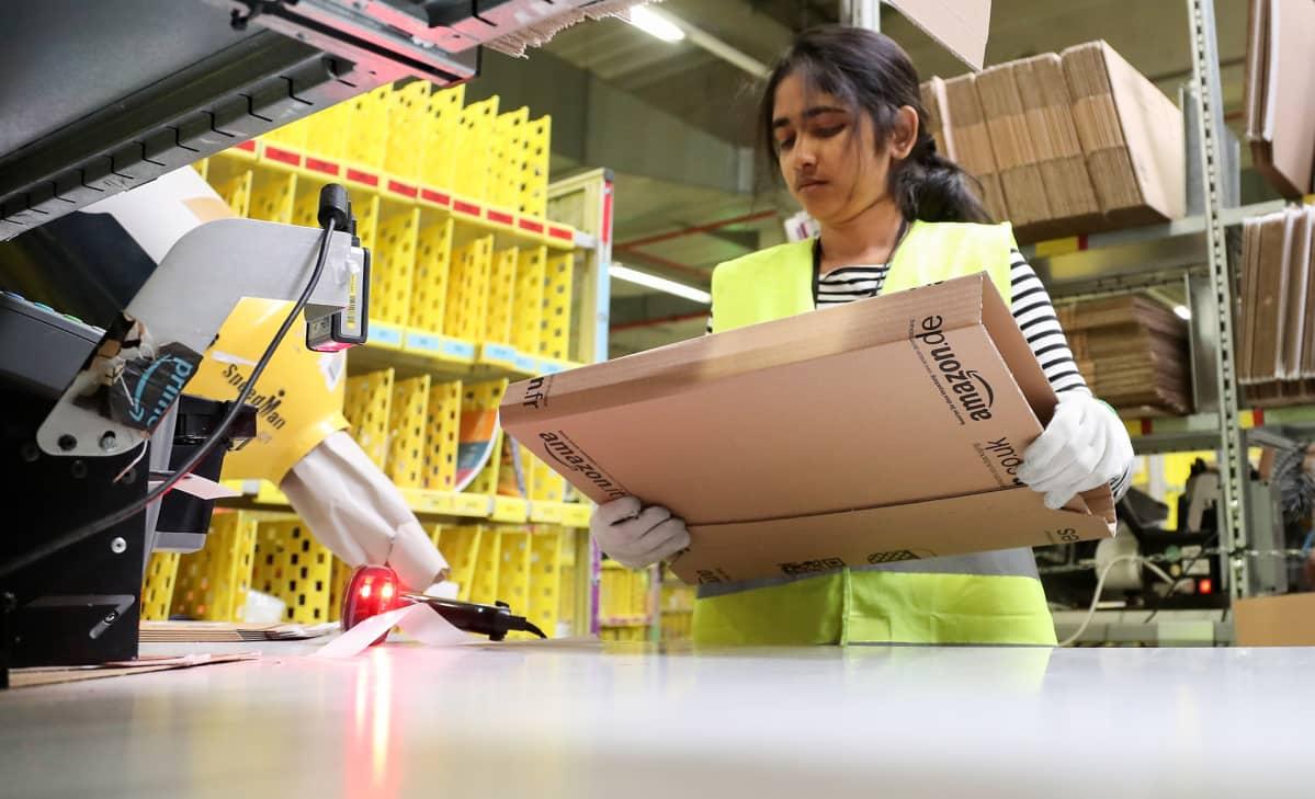 Nainen valmistelee postipakettia valmiiksi.