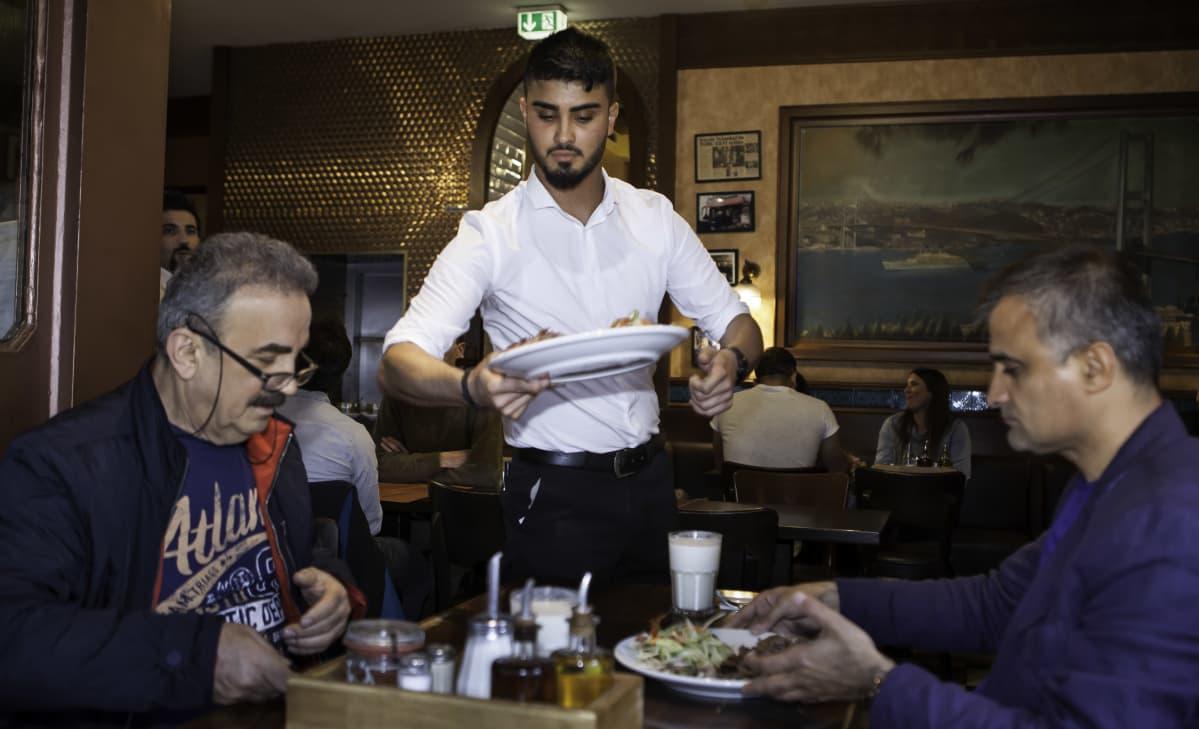 Sarica ojentaa lautasta pöytään, jossa istuu kaksi miestä. Saricalla on lyhyt siististi leikattu parta, valkoinen paita ja mustat housut.