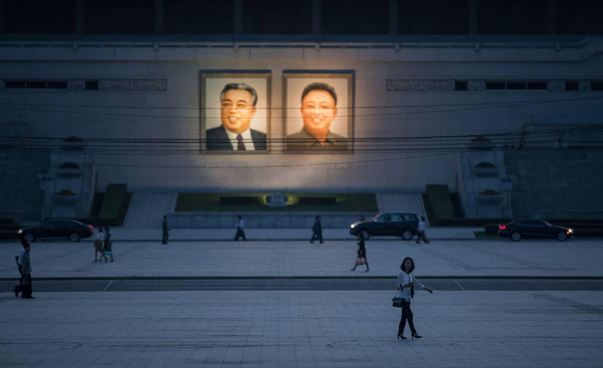 Katunäkymä Pjongjangissa 12. kesäkuuta - taustalla entisten Pohjois-Korean johtajien Kim Il Sung:n (vas.) ja Kim Jong Il:n kuvat.