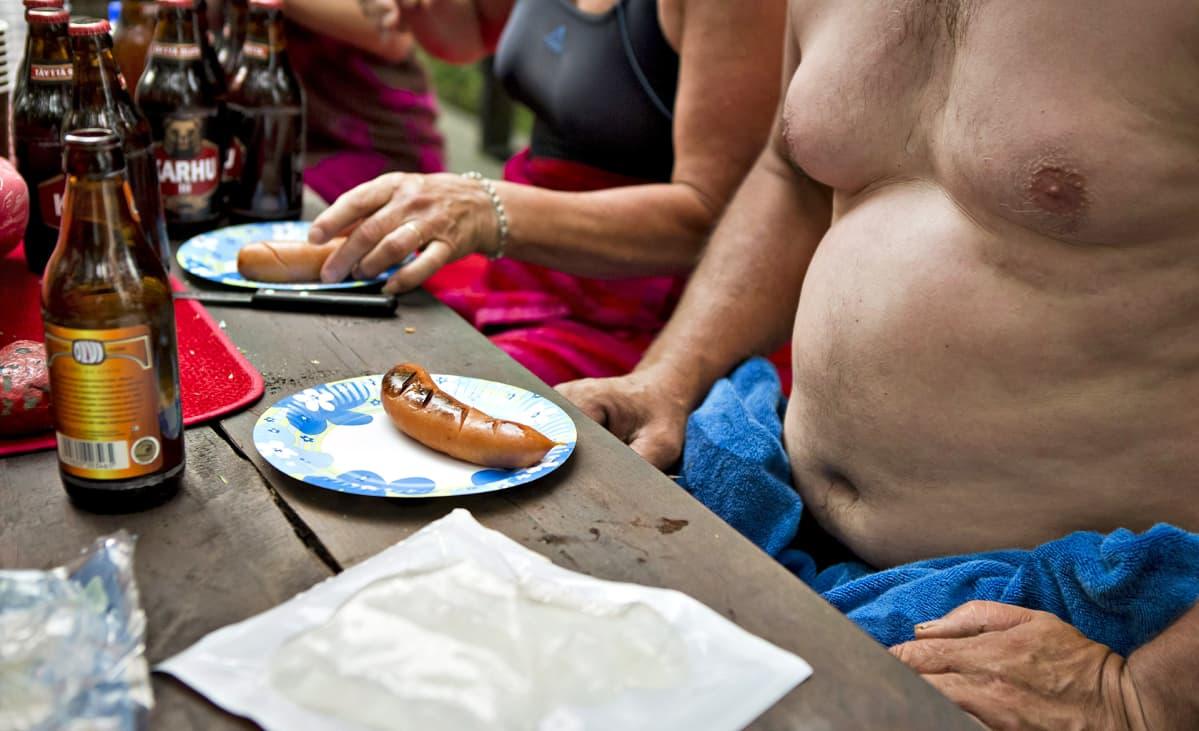 Mies juo olutta ja syö makkaraa saunan terassilla.