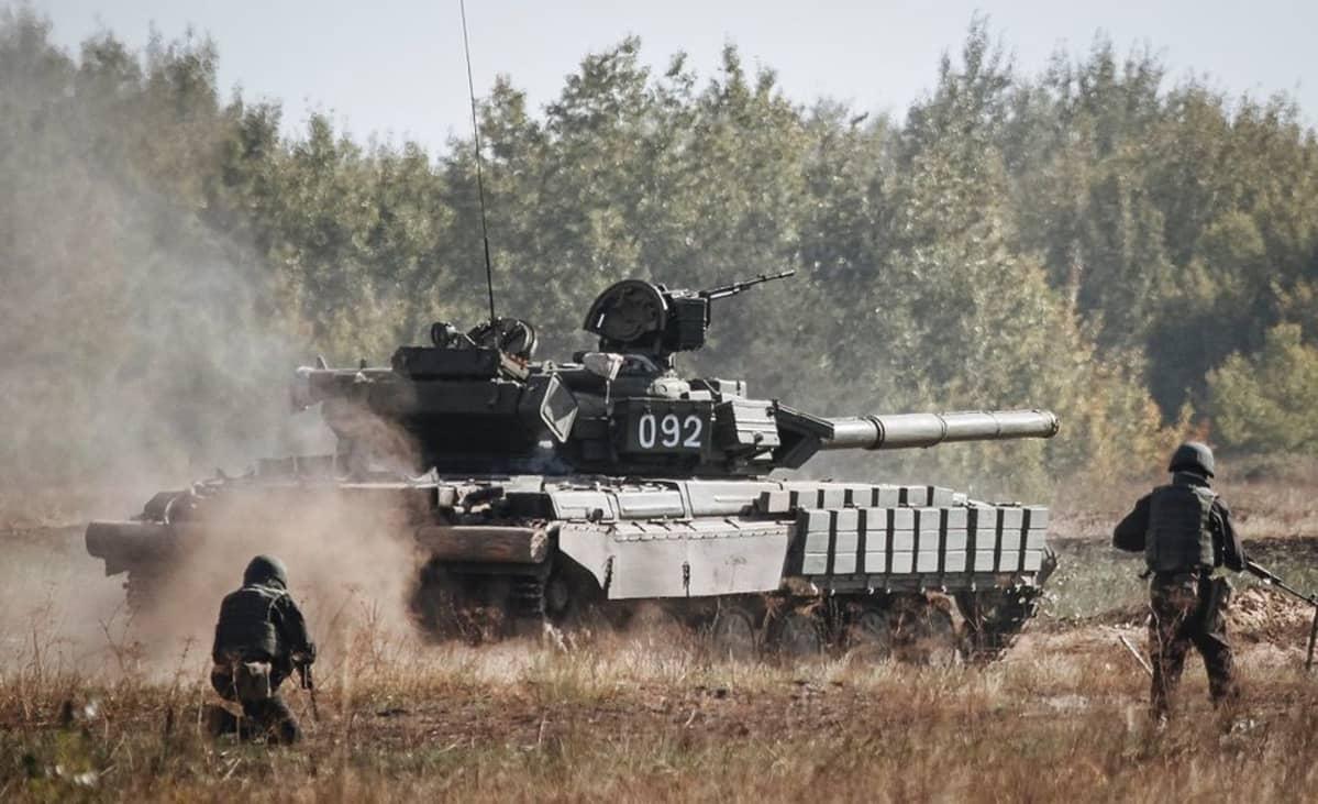 Ukrainan panssarivaunu ja ryhmä sotilaita harjoittelee hyökkäystä maastossa.