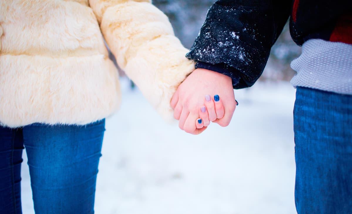 pariskunta pitelee toisiaan kädestä