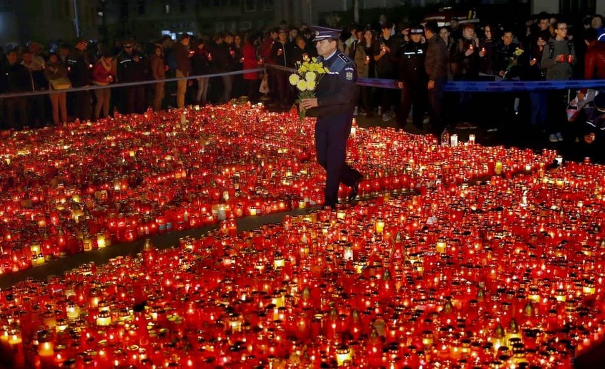 Poliisi kantaa kukkakimppua tulipalon uhrien muistoksi sytytettyjen kynttilöiden keskellä.