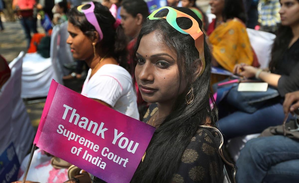 """Hymyileviä ihmisiä. Yhdellä on lippu, jossa lukee """"Kiitos, korkein oikeus."""""""