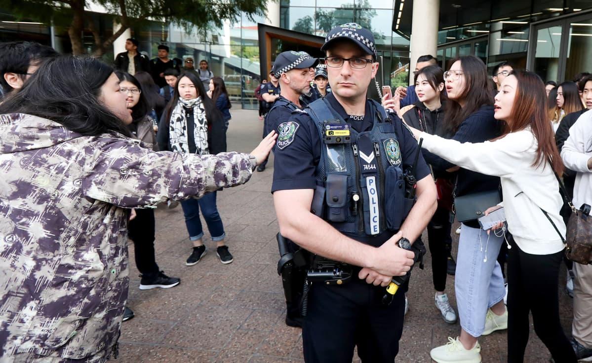 Australian poliisi seisoo protestoijien välissä.