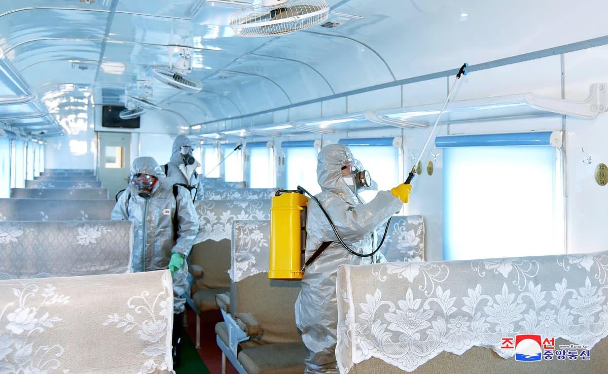 Desinfiointipartio puhdistaa junanvaunua Pjongjangissa Pohjois-Koreassa.