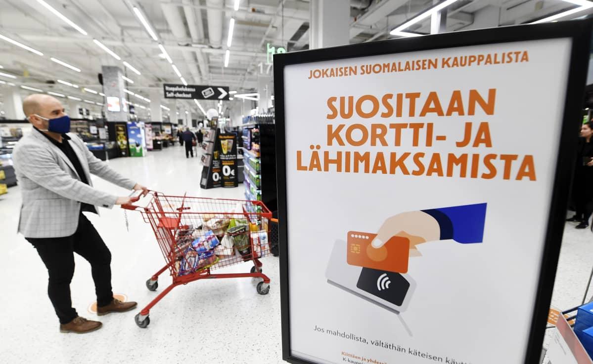 Hengityssuojainta käyttävä asiakas ja suositus korttimaksamisesta uudistetussa K-Citymarket Jumbossa Vantaalla 9. lokakuuta 2020.