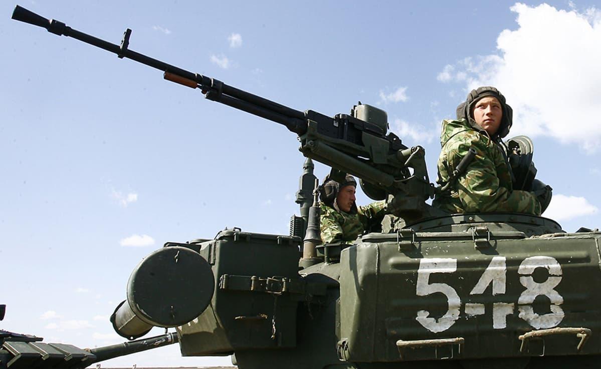 Venäläiset sotilaat istuskelevat sotilastankin päällä.