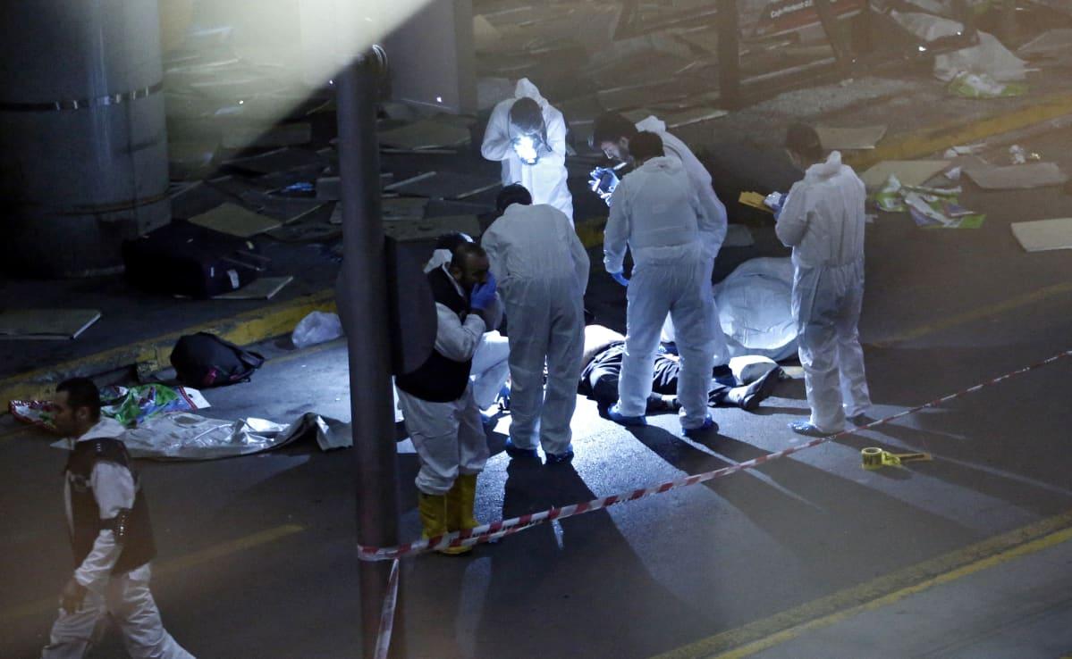Valkoasuiset miehet ovat kerääntyneet maassa makaavan ruumiin ympärille. Kaksi miestä ottaa kuvia ruumiista.