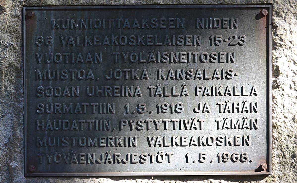 Muistolaatassa teksti: Kunnioittaakseen niiden 36 valkeakoskelaisen 15-23 vuotiaan työläisneitosen muistoa, jotka kansalaissodan uhreina tällä paikalla surmattiin 1.5.1918 ja tähän haudattiin, pystyttivät tämän muistomerkin Valkeakosken työläisjärjestöt 1.5.1968.