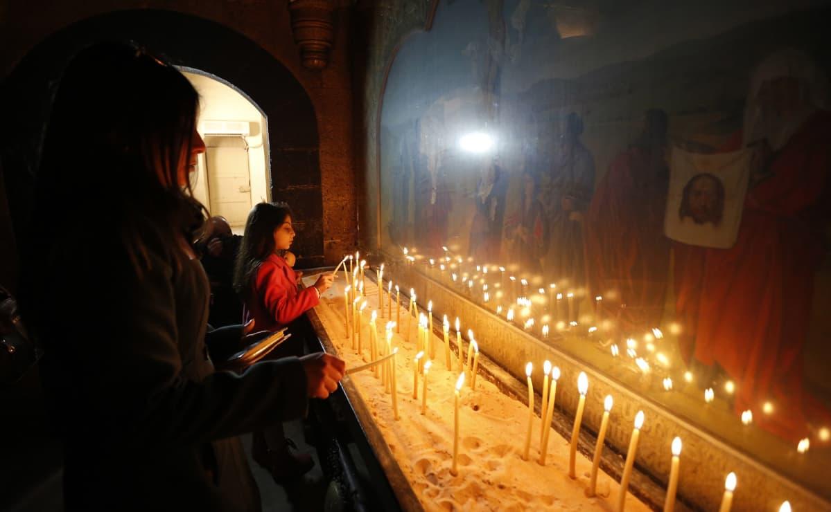 Tyttö sytyttää kynttilöitä