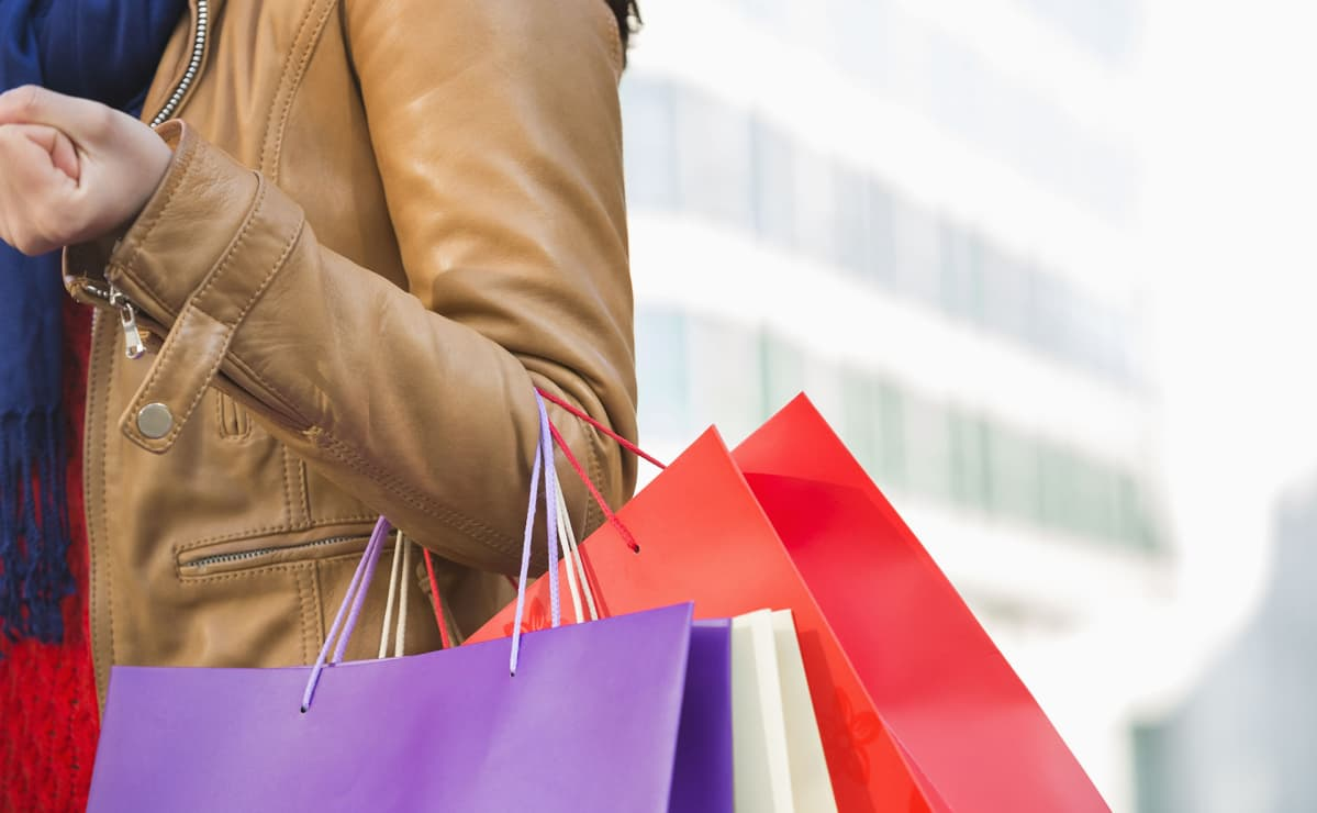 nainen kantaa ostoskasseja