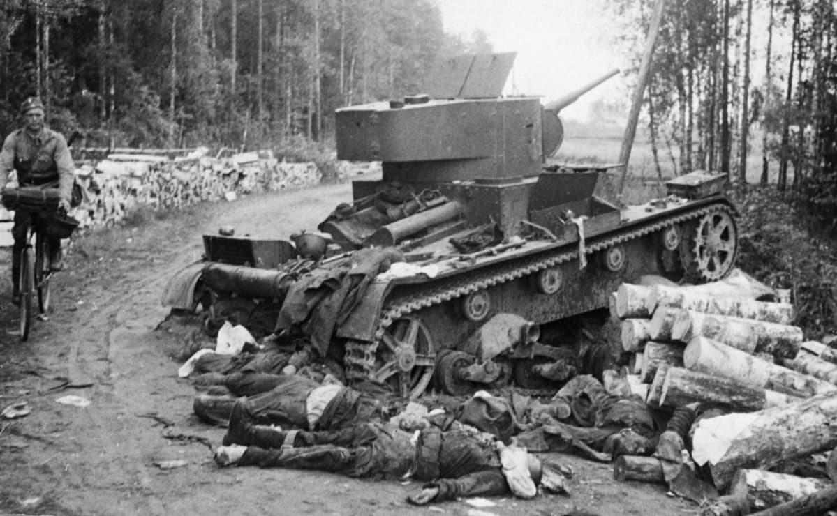 Tuhoutunut panssarivaunu tienposkessa. Tiellä pyöräilee sotilas. Tankin edessä ruumiita maassa.