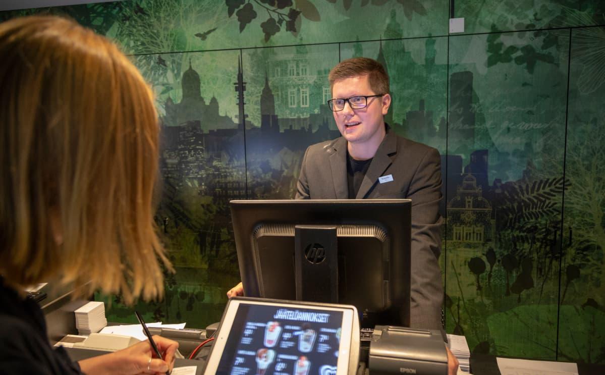 Vastaanottovirkailija työskentelee hotellin aulassa.