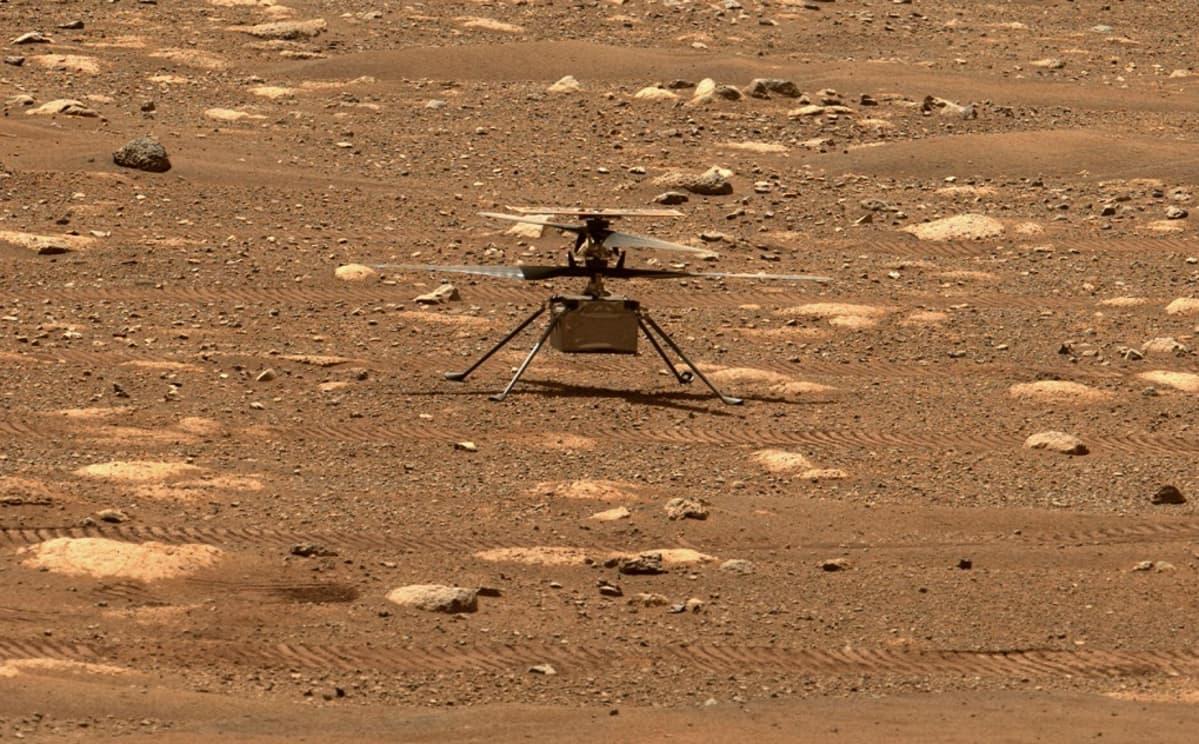 Laatikon muotoinen helikopteri seisoo neljällä ohuella jalalla Marsin kivisellä pinnalla.