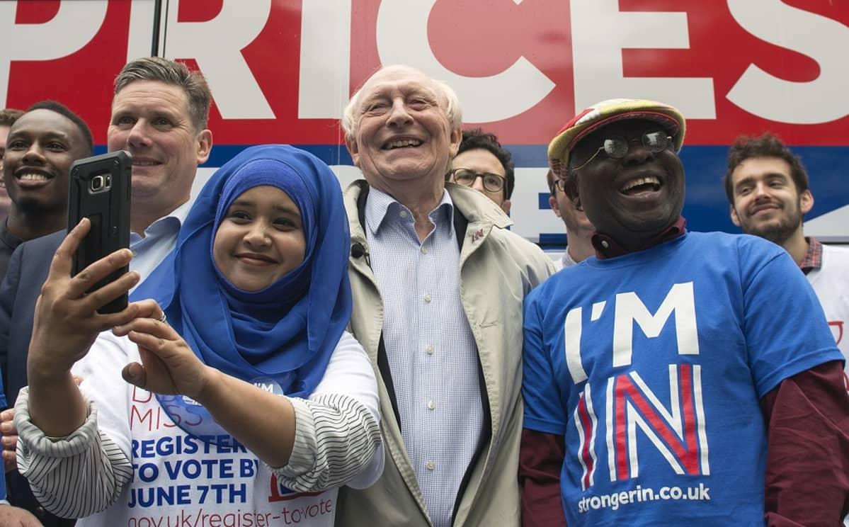 Kinnock hymyilee kannattajien keskellä. Nuori nainen ottaa selfietä.