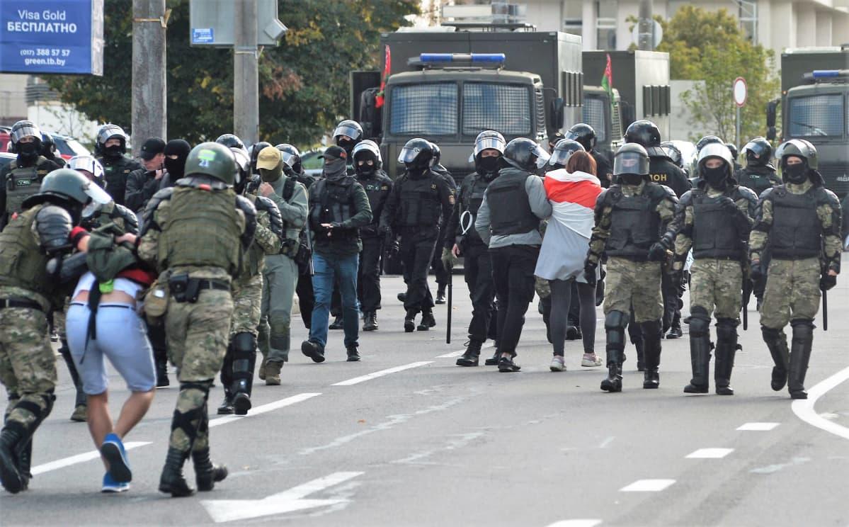 Kadulla kulkee suuri määrä mellakkapoliiseja eri suuntiin. Kaksi ryhmää poliiseista raahaa kahta mielenosoittajaa kohti maastonvihreitä kuorma-autoja.