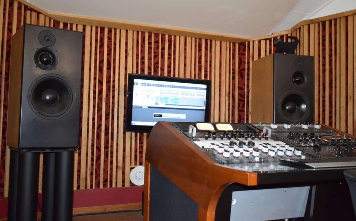 Masterointistudiossa on äänipöytä keskellä ja isot kaiuttimet