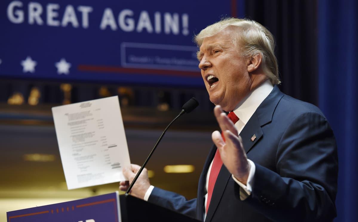 Donald Trump heiluttaa varallisuuttaan esittelevää paperia ilmoittaessaan pyrkivänsä Yhdysvaltain presidentiksi Trump Towerissa, New Yorkissa, 16. kesäkuusa 2015.