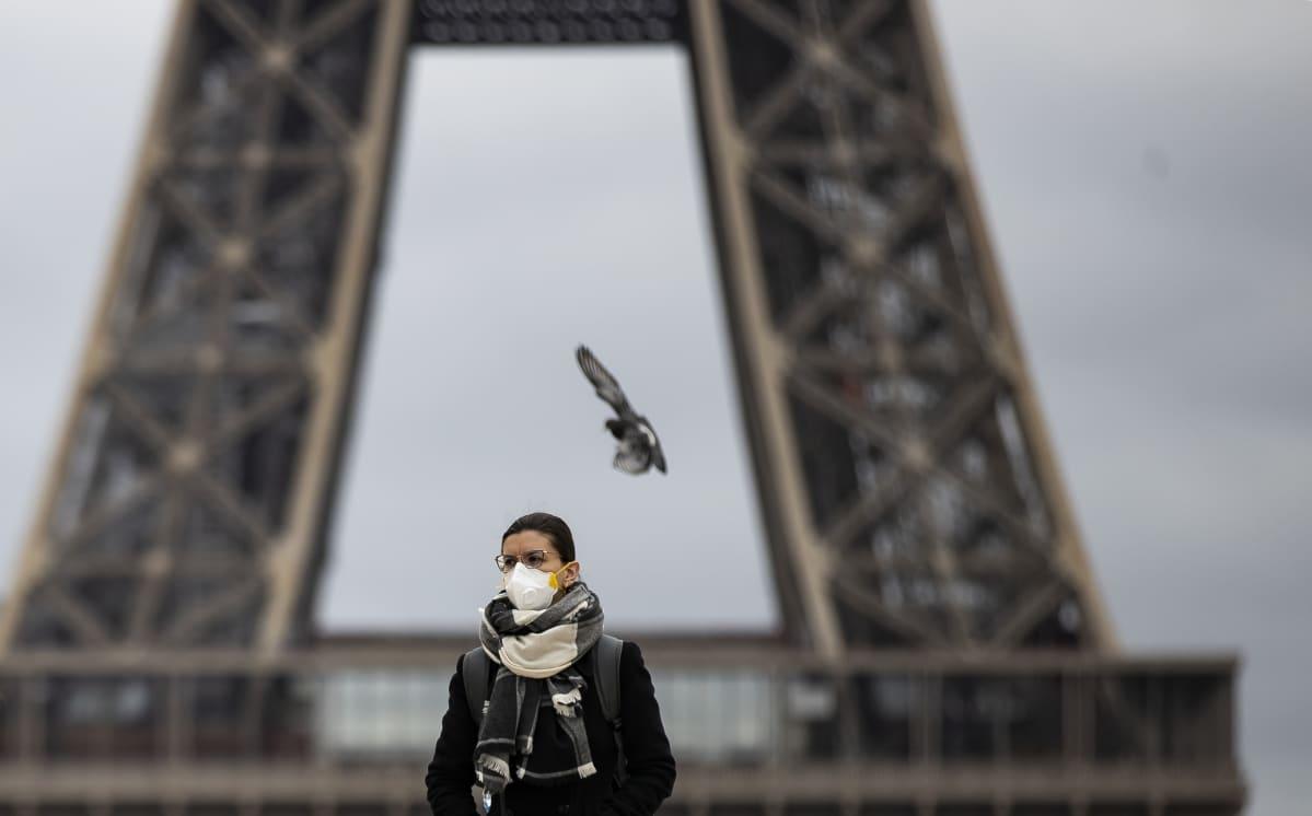 Hengityssuojaan pukeutunut nainen seisoo Eiffel-tornin edessä.