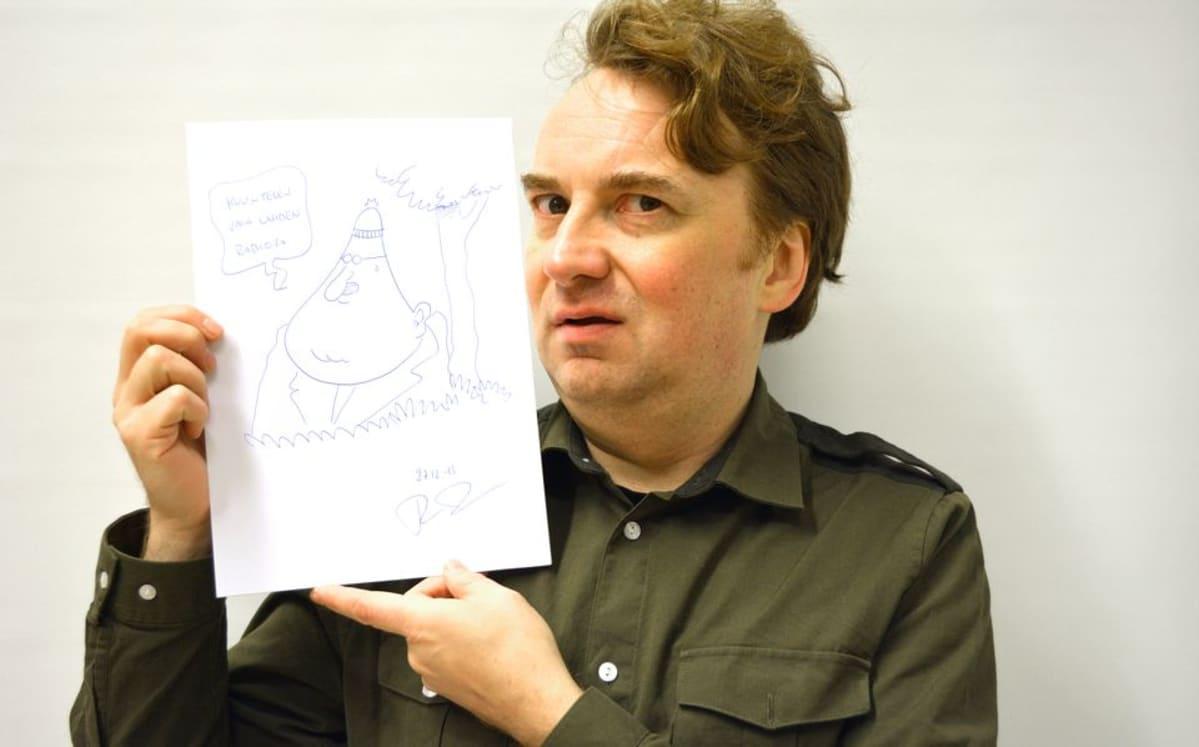 Pertti Jarla esittelee piirtämäänsä kuvaa.
