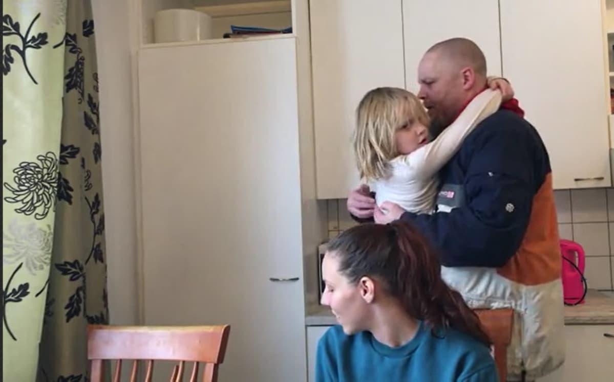 lapsi ja isää halaa äiti katsoo