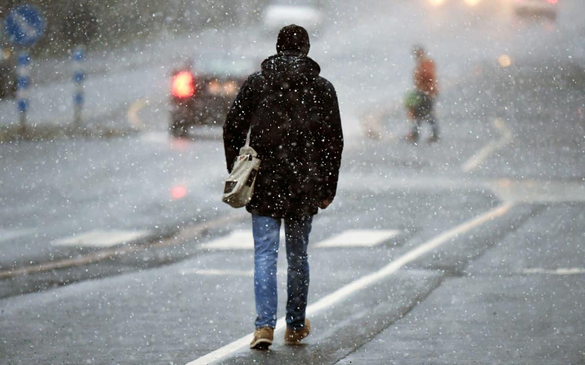 Jalankulkija lumisateessa Hämeenlinnassa.