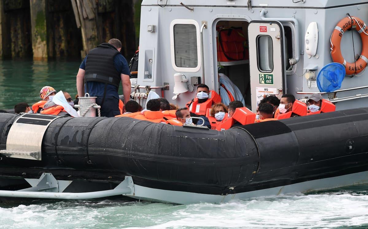 Joukko siirtolaisia pelastusliiveissä laivan kannella.
