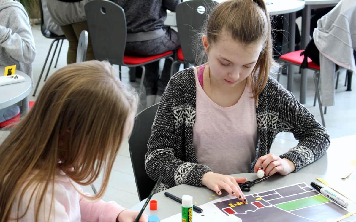 Pinja Uotinen (vas), 11, ja Neea Groschup, ovat suunnitelleet maahan piirrettävää labyrinttiä, josta tulee mahdollisesti jalkapallonmuotoinen.
