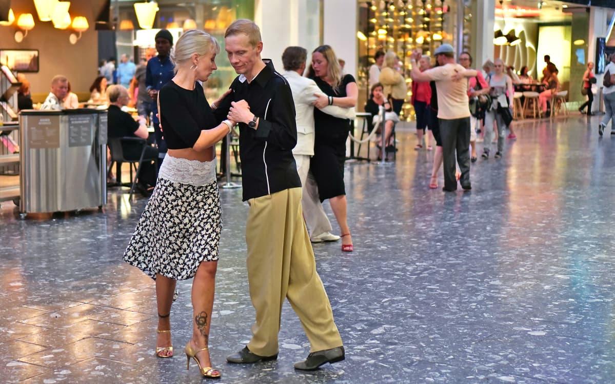 Ihmisiä tanssimassa tangoa kauppakeskuksessa