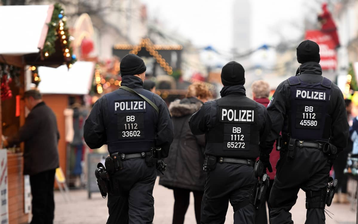 Poliiseja kävelee kadulla, taustalla joulukojuja.