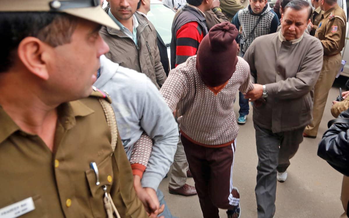 Poliisit kuljettavat huppupäistä raiskauksesta epäiltyä New Delhissä 2014