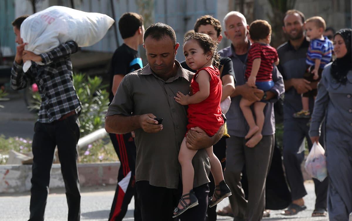 Palestiinalaiset pakenivat kodeistaan Gazassa Israelin iskujen seurauksena 13. heinäkuuta 2014.