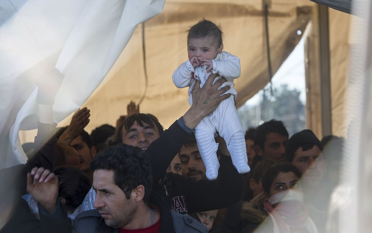 A refugees man lift up his child as he and others await permission to enter Macedonia, near Gevgelia, The Former Yugoslav Republic of Macedonia, 05 March 2016.