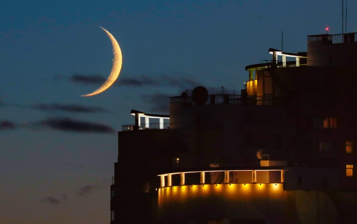 Kuun sirppi rakennuksen kattoterassien yllä