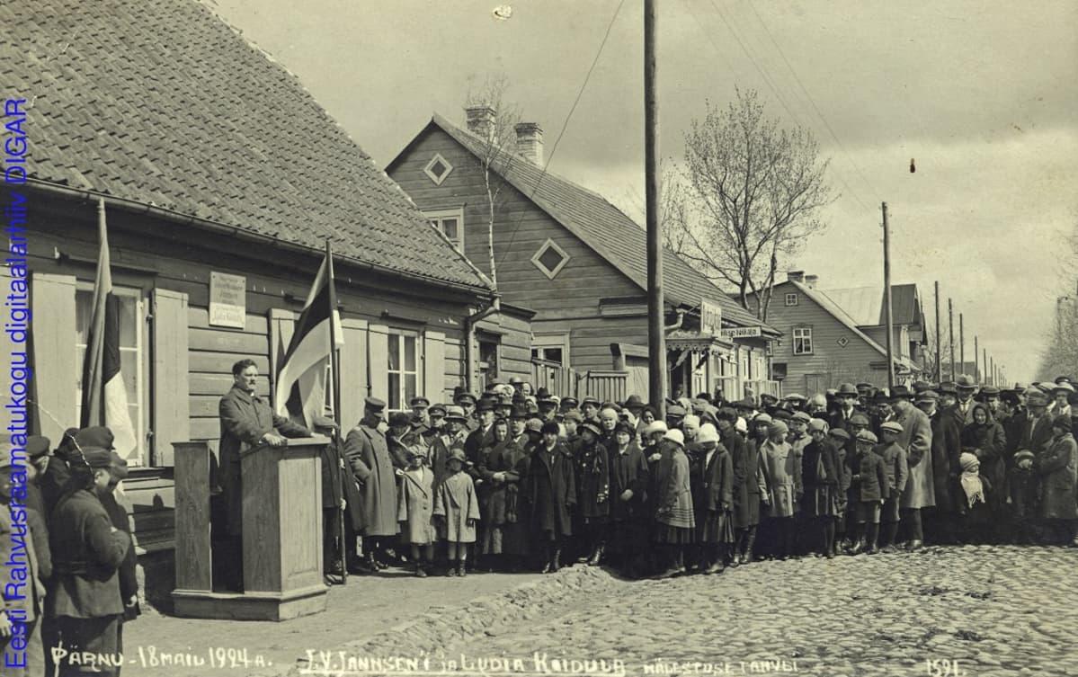 Mustavalkoinen valokuva väkijoukosta, joka seisoo kuuntelemassa puhujapöntössä olevaa miestä. Mukulakatu,puutaloja ja salossa Viron lippu.