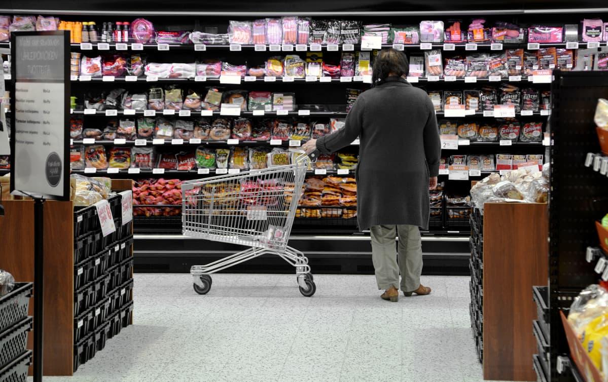 Nainen tutkii hyllyä ruokakaupassa.