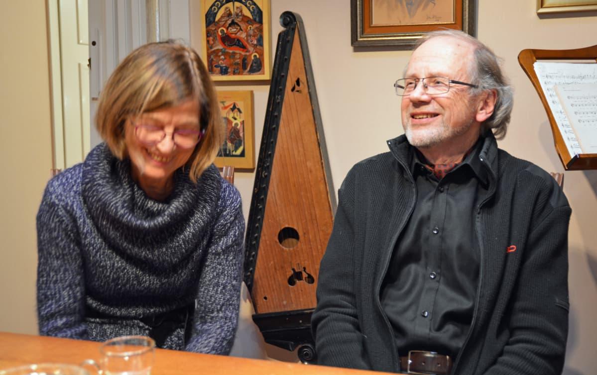 Mies ja nainen nauravat pöydän äärellä