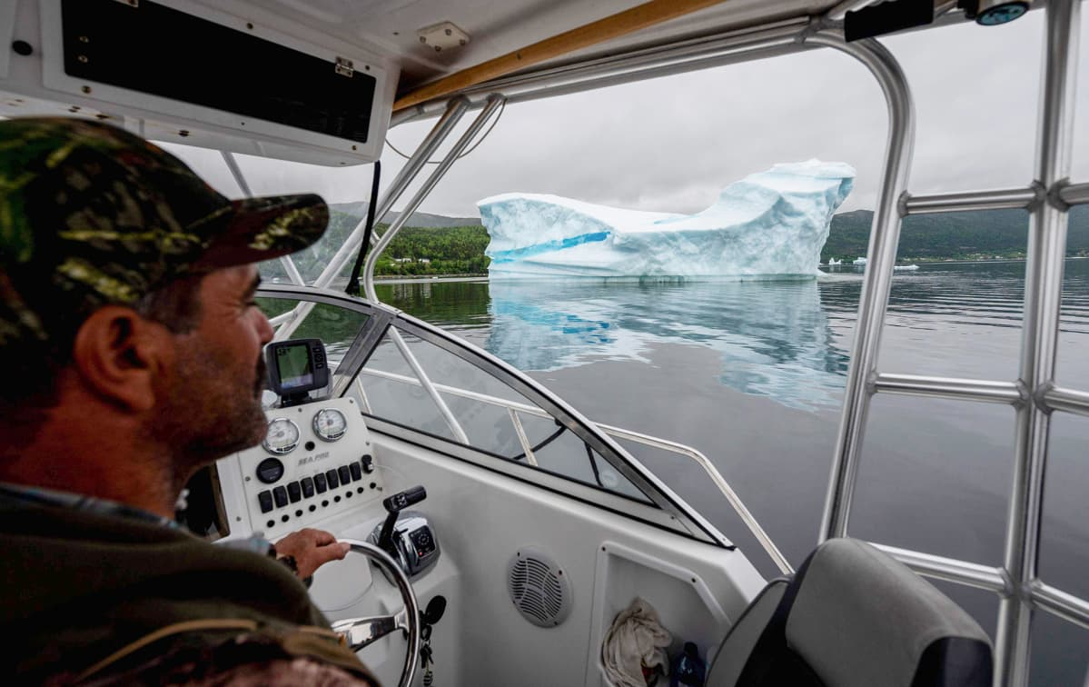 Entinen kalastaja ja nykyinen turistiopas veneessään jäävuori taustalla.