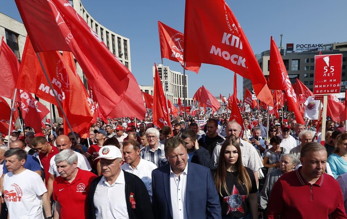 Mielenosoitusmarssi etenee leveällä kadulla. Mielenosoittajat kantavat suuria punalippuja.