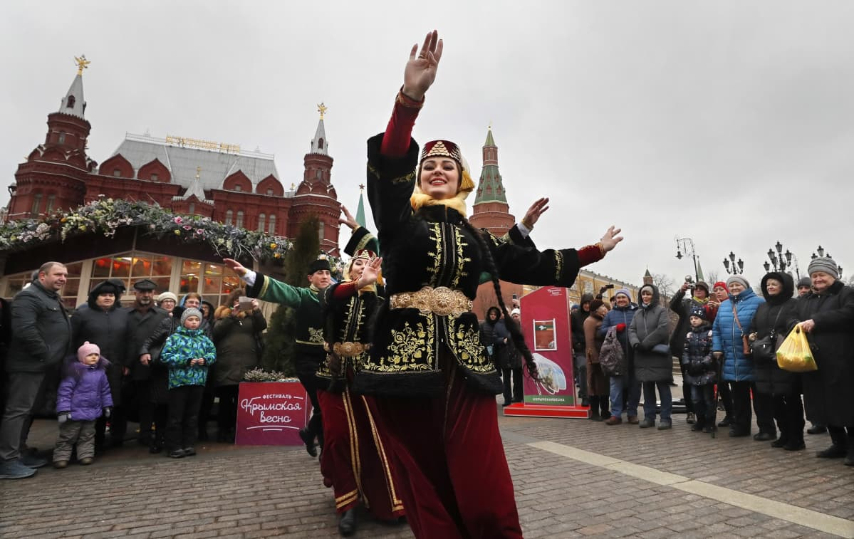 Kansallispukuisia naisia tanssii ihmisten keskellä