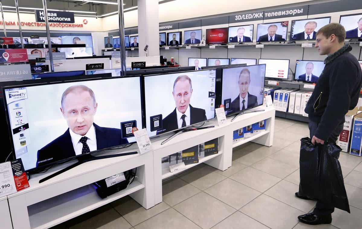 Venäläinen mies katsoo Putinin puhetta televisiosta elektroniikkakaupassa.