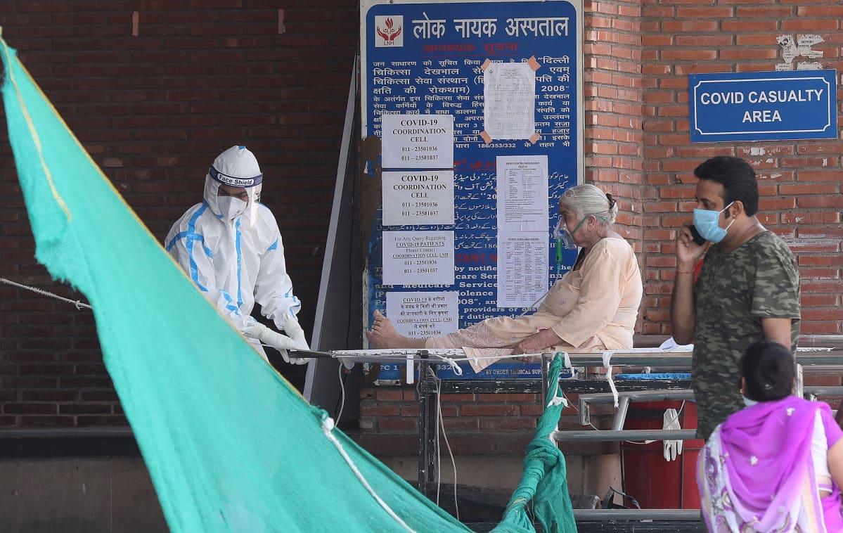 Iäkäs nainen siirretään korona-sairaalaan Delhissä kesäkuussa 2020.