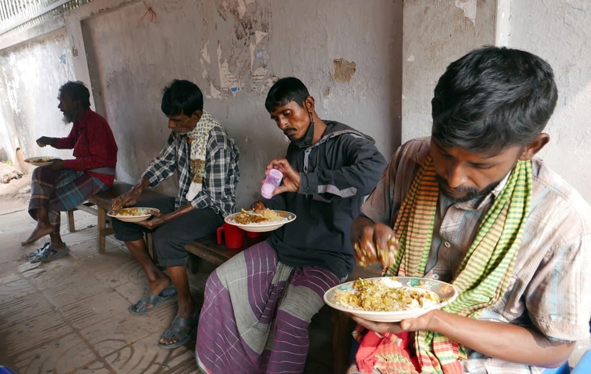 Kuvassa neljä miestä syömässä.