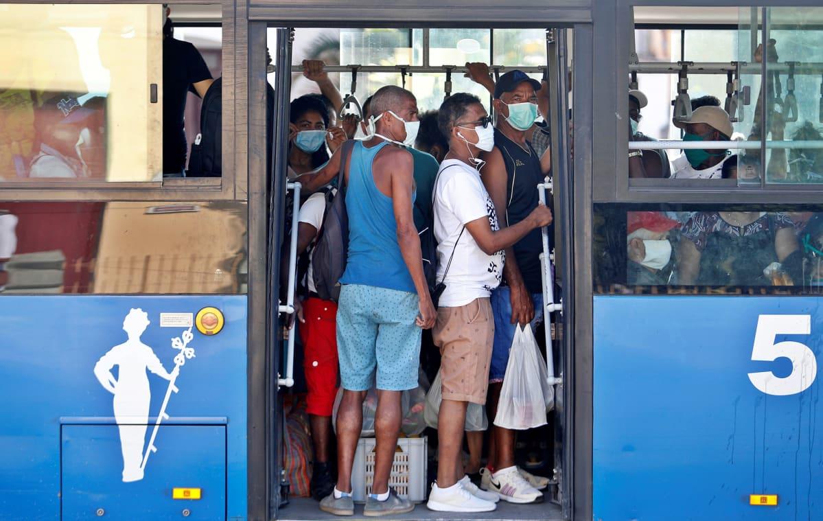Kasvomaskeihin pukeutuneita matkustajia bussin kyydissä.