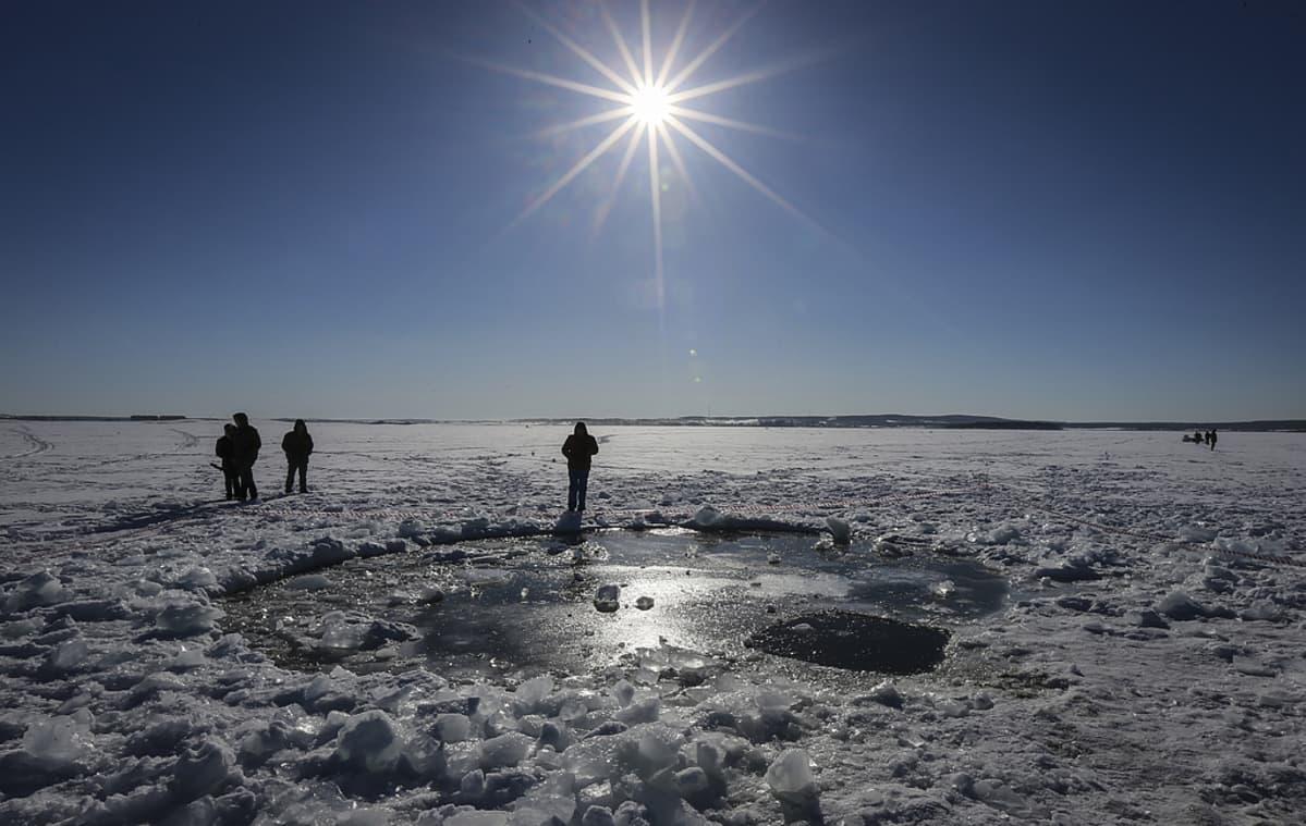 Ihmisiä todennäköisesti meteoriitin aiheuttaman avannon ympärillä Tsherbakuljärven jäällä.